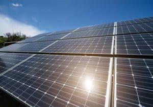 solar panels against blue sky with sunlight 300x211